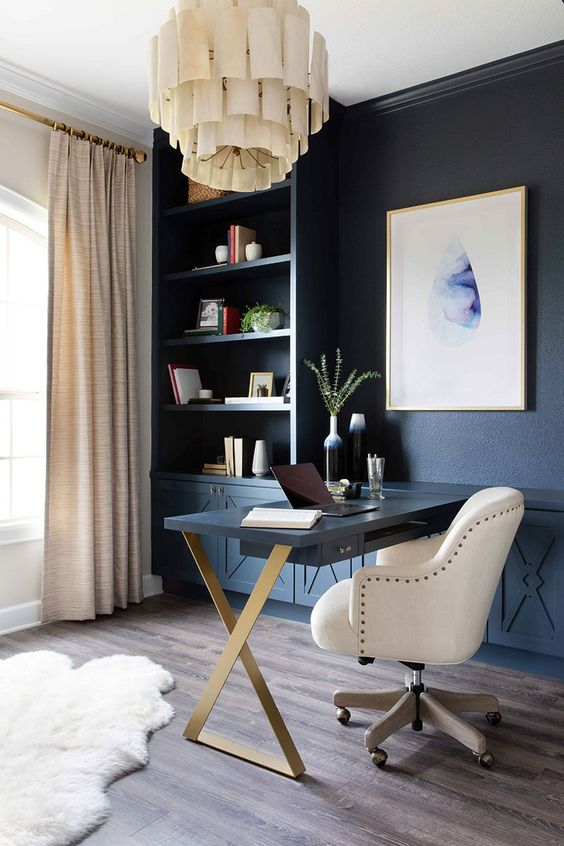 a chic home office with a blue wall taken by storage units, a statement artwork, a unique chandelier, a Murphy desk and a large white chair