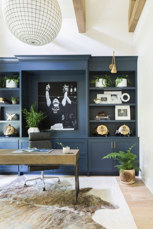 a chic home office with a whole wall in blue taken by a large storage unit, a wooden desk and a large lamp plus touches of gold