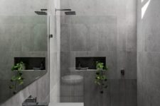 a chic minimalist grey bathroom with large scale tiles, a grey vanity with a round sink and some potted greenery