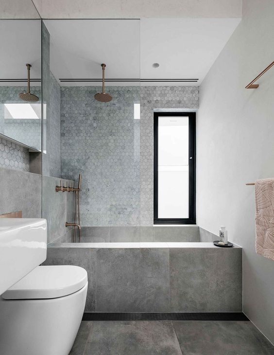 a chic minimalist grey bathroom with marble hex tiles, large scale grey ones and copper fixtures for a warmer touch