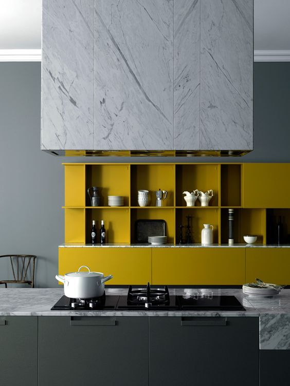 a chic minimalist kitchen with a black kitchen island, mustard cabinetry, white marble touches looks fantastic