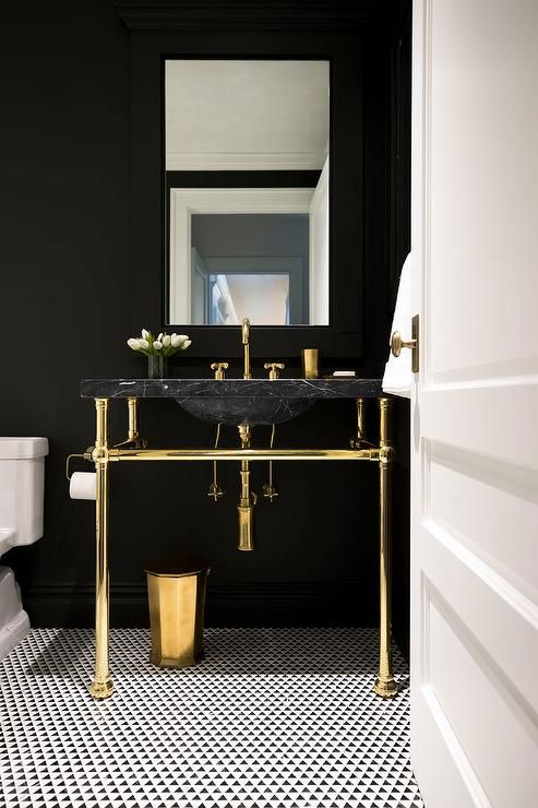 a chic powder room with black walls, a black marble sink, gold fixtures and legs plus a mosaic tile floor