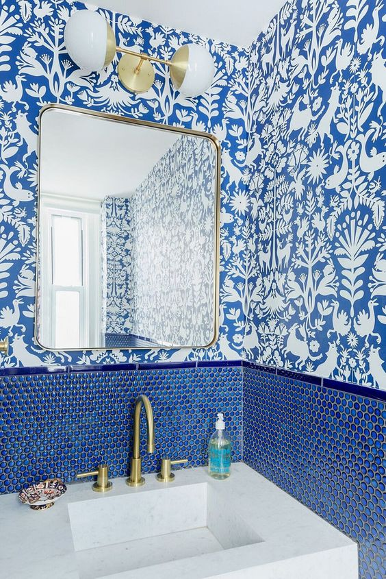 a chic powder room with blue and white wallpaper, blue penny tiles, gold fixtures and lamps plus a stone sink