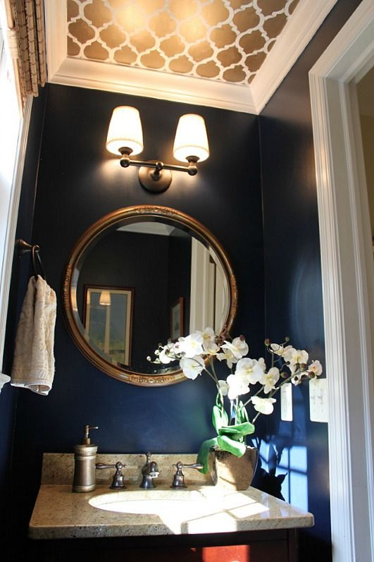 a chic powder room with navy walls, a stenciled gold and white ceiling, a gold frame mirror, a sconce and a stone sink