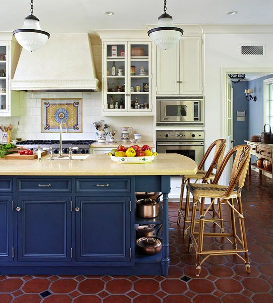 a chic traditional kitchen with light yellow walls, cabinets and a navy kitchen island plus tiles on the floor