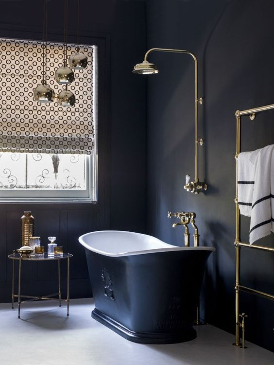 a chic vintage bathroom with black paneled walls, a black tub, gold fixtures, printed shades and gold accessories