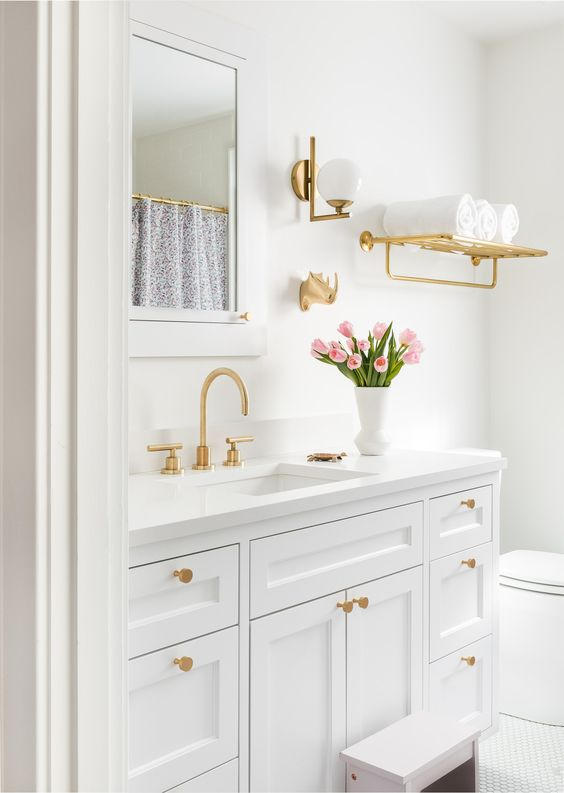 a chic white bathroom with gold fixtures, knobs, a shelf and sconces is a pretty space