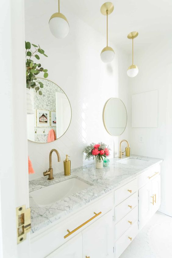 a chic white bathroom with gold pendant lamps, gold handles, fixtures and round mirrors in gold frames