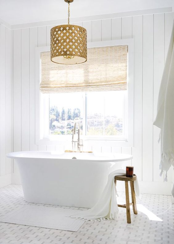 a chic white bathroom with shiplap walls, a mosaic tile floor, a tub by the window and a fabric covered vanity