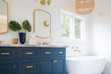 a coastal bathroom with blue and white printed tiles, a blue and gold vanity, gold frame mirrors, a woven lamp and a free-standing tub