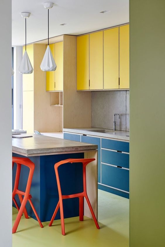 a colorful modern kitchen done in yellow and navy, with a stone countertop, red stools and a green floor is extra bold