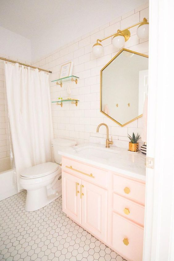 a contemporary bathroom clad with white tiles, with a light pink vanity, gold fixtures, knobs and a geometric mirror