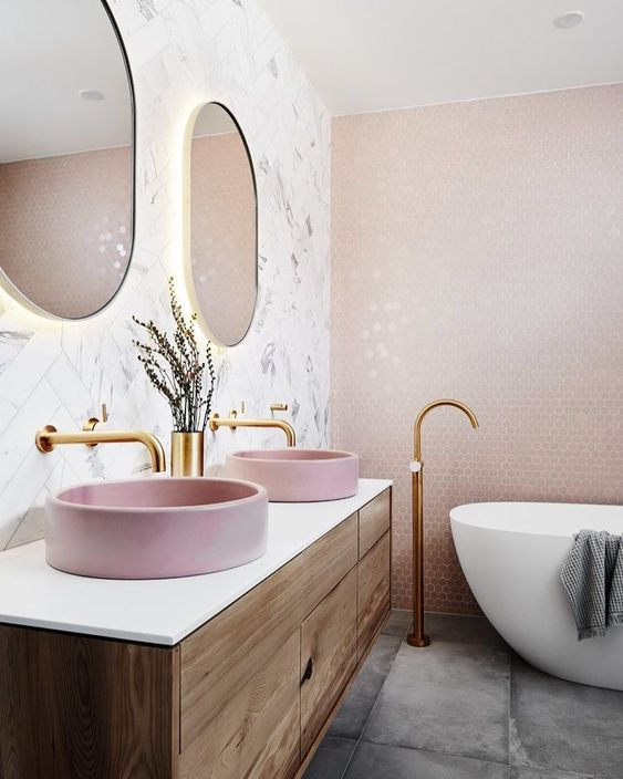 a contemporary bathroom with blush hex tiles on the wall, pink sinks, glam fixtures and lit up gold frame mirrors