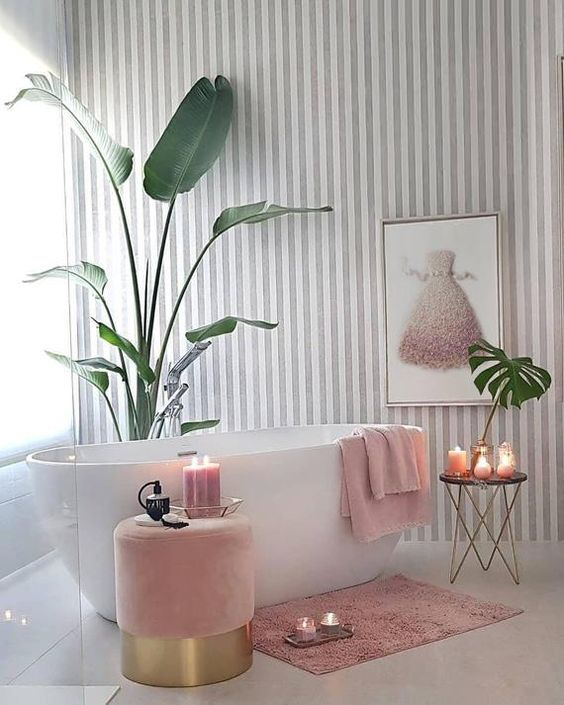a contemporary glam bathroom with a striped wallpaper wall, a pink dress artwork, pink towels and an ottoman, a pink rug and candles plus touches of gold