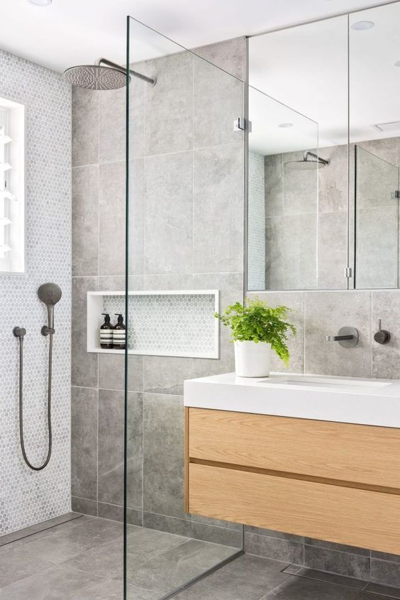 a contemporary grey bathroom clad with large scale tiles and penny ones, with a floating wooden vanity and a large window