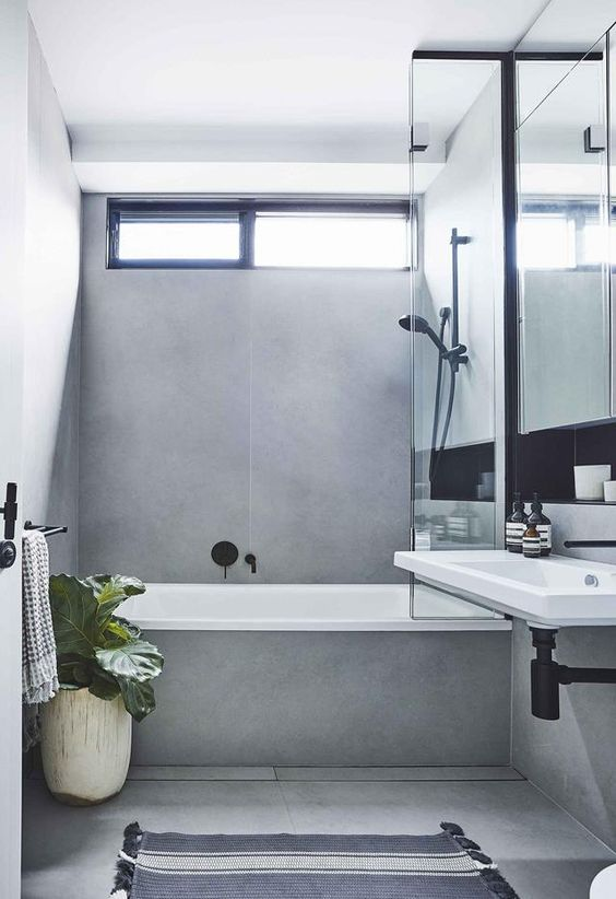 a contemporary grey bathroom clad with large scale tiles, with a small window and black fixtures to make it look bolder