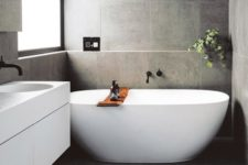 a contemporary grey bathroom clad with tiles, with a floating vanity and an oval tub plus greenery to refresh the space