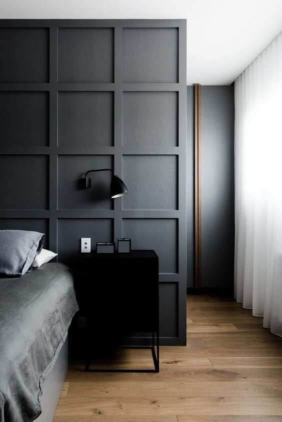 a contemporary mmoody bedroom with a statement graphite grey paneled wall that separates the sleeping space from the closet