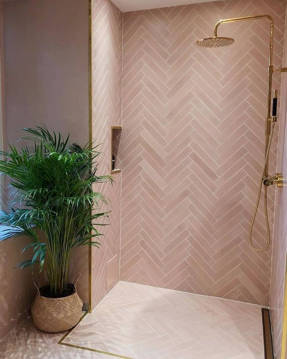 a contemporary pink bathroom clad with pink tiles in a herringbone pattern, gold fixtures and frames for a glam look