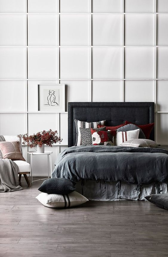 a contrasting bedroom with a white paneled wall, a blakc upholstered bed, dark bedding and a white chair looks ultra-modern