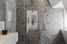 a cool minimalist grey bathroom with grey terrazzo in the shower, a white vanity and windows for natural light