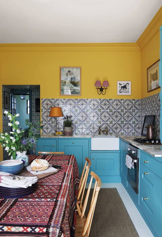a cozy small kitchen with bright yellow walls and mosaic tiles on the backsplash, bright blue cabinets and vintage wall sconces