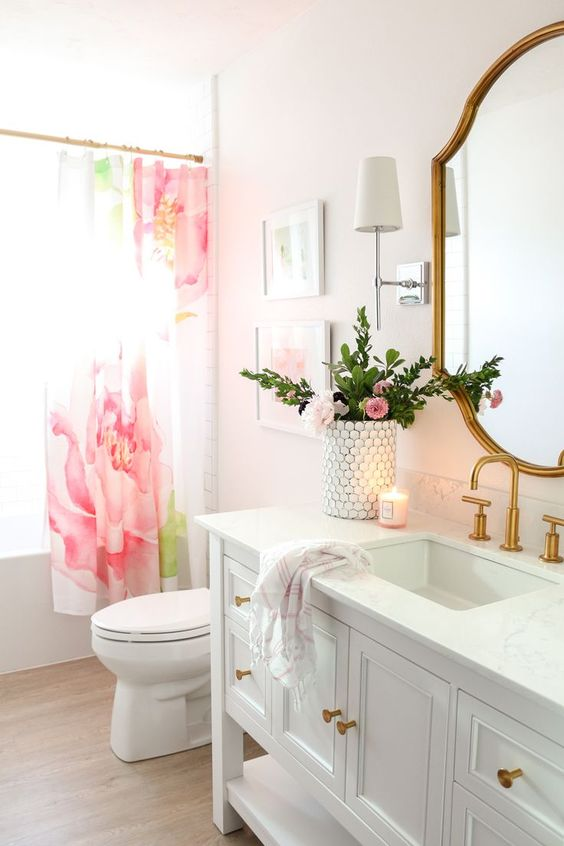a cute glam bathroom with blush ombre walls, a pink flower curtain, gold fixtures and a chic gold frame mirror plus pink blooms