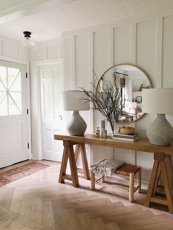 a farmhouse entryway with white paneled walls, wooden furniture, chic lamps and much natural light