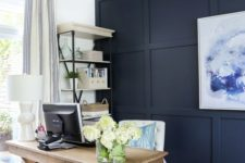a farmhouse home office with a navy paneled wall, a bold artwork, a wooden desk and a basket plus a storage unit