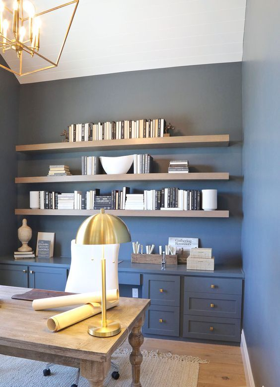 a farmhouse home office with blue walls, wooden shelves and a vintage desk, gold lamps and knobs for a touch of chic