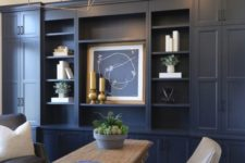 a farmhouse home office with navy walls – one of them taken by a storage unit, neutral furniture and gold touches for more elegance
