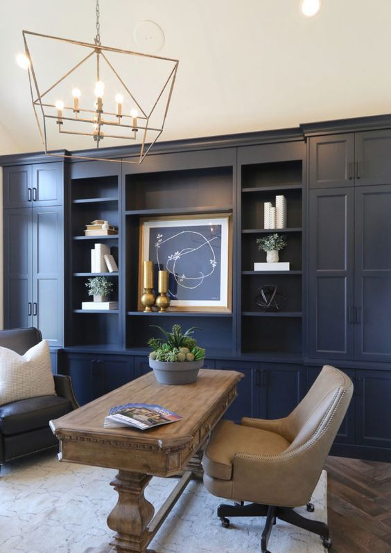 a farmhouse home office with navy walls - one of them taken by a storage unit, neutral furniture and gold touches for more elegance