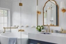 a floor clad with blue and white mosaic tiles, a blue vanity, gold fixtures, gold lamps and a bold printed sink