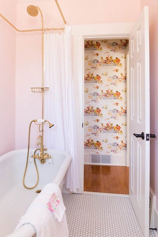 a glam bathroom with light pink walls, gold fixtures and cute floral towels with pink touches