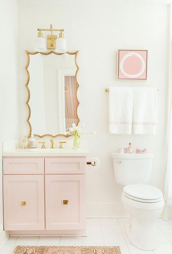 a glam contemporary bathroom with a light pink vanity, artwork and accessories, gold fixtures and a a catchy mirror in a gold frame