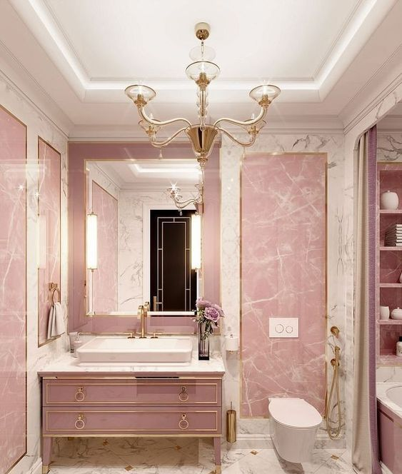 a glam pink bathroom done with stone and marble, with a refined pink vanity, a vintage chandelier and gold fixtures
