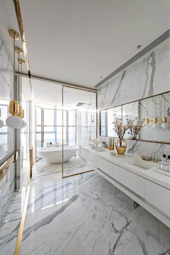 a glam white bathroom all done with marble, with pendant gold lamps, gold frames and a mirror in a gold frame