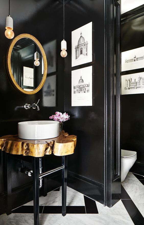 a gorgeous bathroom with a mosaic tile floor, black walls, a gold frame mirror, a wood slice vanity and artworks