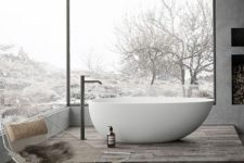 a gorgeous grey bathroom done with concrete, with glazed walls, a fireplace and a tub on a platform