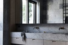 a gorgeous minimalist grey bathroom made of stone slabs, with an oversized mirror and a cool oval tub
