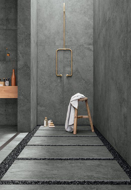 a grey concrete bathroom with pavement tiles and gravel on the floor plus gold fixtures to add chic to the space