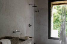 a grey wabi-sabi bathroom with concrete walls, grey tiles, stone sinks and a large window to enjoy the views
