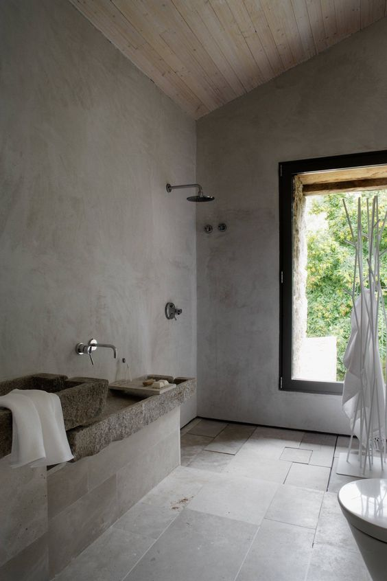 a grey wabi-sabi bathroom with concrete walls, grey tiles, stone sinks and a large window to enjoy the views