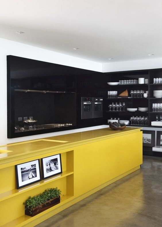 a large contemporary kitchen done with black cabinetry and walls plus a bright yellow kitchen island for a contrast