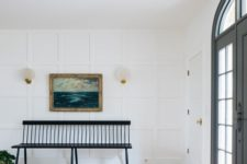 a large entryway with a white accent paneled wall that doesn't look boring but catches an eye and looks chic