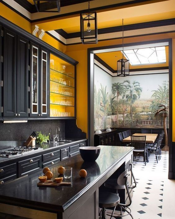 a large vintage kitchen done with yellow walls, black cabinetry and vintage furniture plus lamps makes a statement