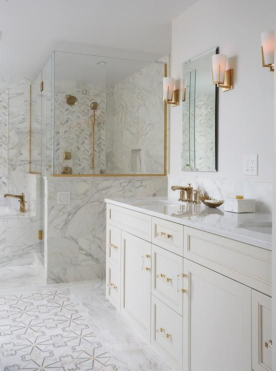 a large white bathroom clad with various types of tiles, with gold handles, fixtures, framing and sconces is a chic space