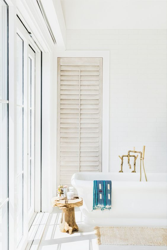 a light-filled white bathroom with a free-standing tub, brass fixtures, a wooden stool and a glazed wall plus shutters