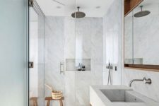 a light grey bathroom fully clad with grey large scale tiles, with touches of wood for warmth and much natural light
