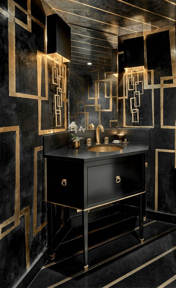 a luxurious black and gold bathroom with a geometric vanity, gold geometric detailing and gold fixtures and candles